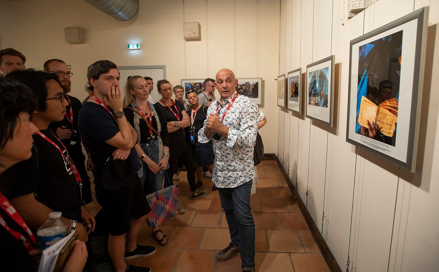 Pascal Maitre gives a tour of his exhibition, covering refugees crossing the Sahel desert. © Paul Hackett
